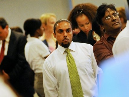 Job seekers wait in line to